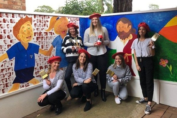 Our-Lady-of-Mt-Carmel-Catholic-Primary-School-Mt-Pritchard-teachers-stand-in-front-of-their-school-art-mural
